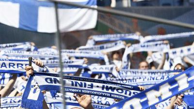 Fotbollssupportrar håller i finländska fotbollshalsdukar.