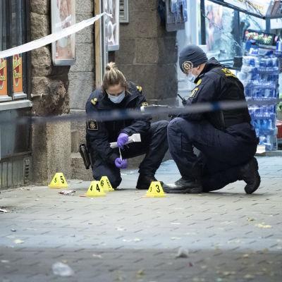 Kaksi poliisia tutkii rikospaikkaa kadulla.