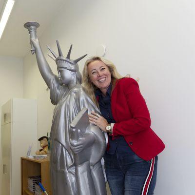 Joe Bidenia äänestävä Lena Grenat halaa nauraen toimiston käytävällä olevaa vapaudenpatsaan pienoismallia.