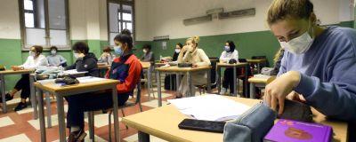 Elever i munskydd sitter i ett klassrum i Italien.