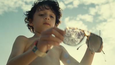 Unga pojken Trent håller upp ett par trasiga solglasögon på stranden.