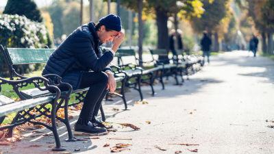 Ung man sitter på en bänk i höstsolen och ser utmattad ut