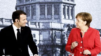 Emmanuel Macron och Angela Merkel tittar på varandra under en presskonferens i Berlin.