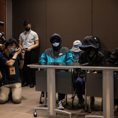 Kaksi ihmistä istuu pöydän takana, molemmilla päässä huppu ja aurinkolasit sekä kasvoilla maski. Vieressä useita valokuvaajia.