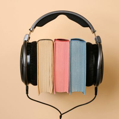 Kuulokkeet ja kolme kirjaa.