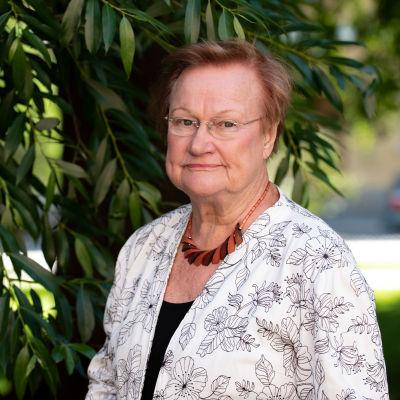 Tarja Halonen seisoo puistossa puun edessä.