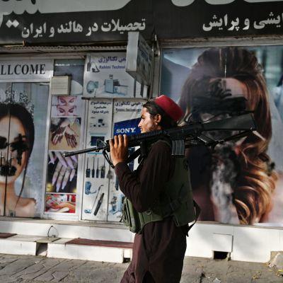 En talibansoldat bär på ett gevär. Han går förbi en affär där ansikten på kvinnor på raklamaffischer målats över.