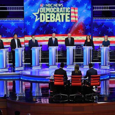 Tio kandidater står på rad vid varsitt podium och debatterar.