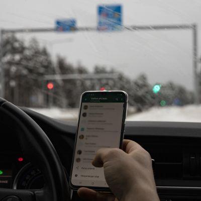 Mies viestittelee puhelimellaan liikennevaloissa.