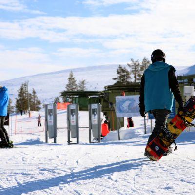 Lasketteluasuinen mies kantaa lumilautaa Ylläksen hissejä kohti. Kuvan vasemmassa laidassa toinen laskija seisoo suksilla.