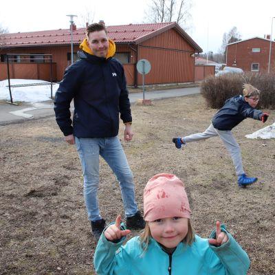Sinitakkinen Mila Hyöppinen näyttää sormilla ylöspäin, taustalla isä Kimmo Hyöppinen ja veli Elmo heittävät frisbeegolfia.