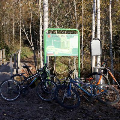 Kariston frisbeegolfradan pääsisäänkäynti. Polkupyöriä runsaasti käyntisillan vieressä.