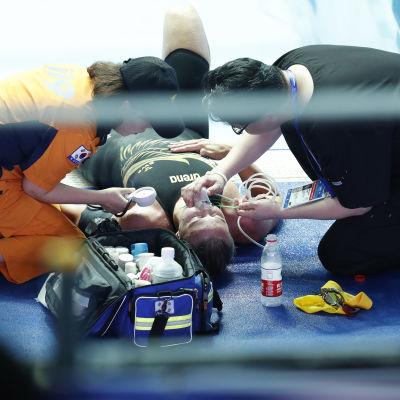 Sarah Sjöström ligger på rygg och får syrgas av läkare.