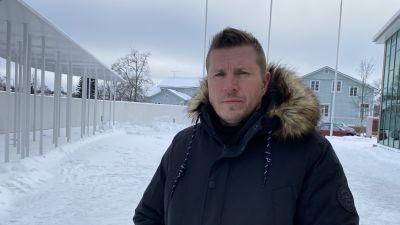 En man iklädd vinterjacka tittar med allvarlig min in i kameran. Miljön är snöig.