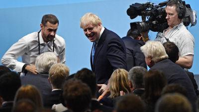Boris Johnson omringad av kameror.