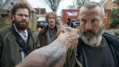 Markus (Mads Mikkelsen) står och stirrar på en man som siktar en pistol mot hans huvud.