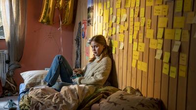Mathilde (Andrea Heick Gadeberg) sitter på sängen i sitt rum och ser allvarlig ut.