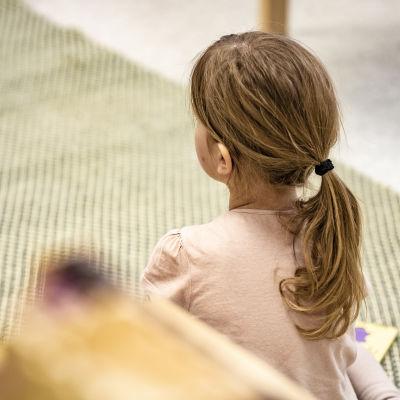 Anonym bild från ett daghem. En flicka sitter på knä med ryggen vänd mot kameran.
