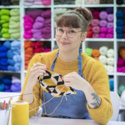 Molla Mills pitelee käsissään virkkuutyötä. Hänen taustallaan on hyllyllinen värikkäitä lankoja.