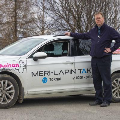 Lapin taksiliiton puheenjohtaja Jussi Rahkonen poseeraa taksiaan vasten.