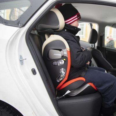 Kouluikäinen lapsi istuu turvaistuimessa pysäköidyn henkilöauton kyydissä.