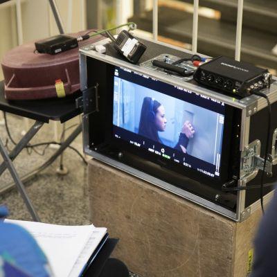 Kaksi tuotantoryhmän jäsentä seuraa tv-monitoria, missä näyttelijä laittaa kaapin ovea kiinni.