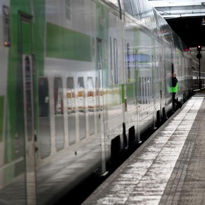 En konduktör syns vid dörren till ett tåg vid Helsingfors centralstation.