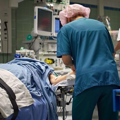 Leikkaussali, potilas, sairaanhoitajia ja lääkäreitä
