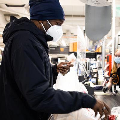 Henkilö pakkaa ruokakaupasta ostamiaan tuoteeita.