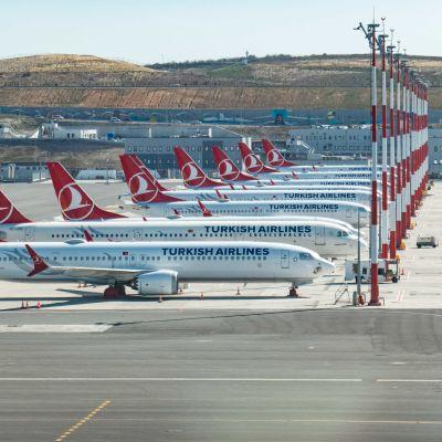 Vita flygplan med röda detaljer står på rad på en enorm flygplats.