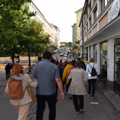 En grupp människor går nerför en gata i Sörnäs, deltar i en guidad rundtur som leds av Pertti Stenman.