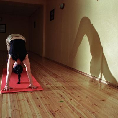 Nainen harjoittaa astangajoogaa.