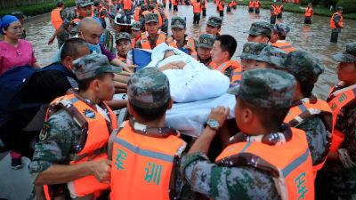 En patient från ett sjukhus i Henan bärs över översvämmade gator på en bår av räddningsmanskap.