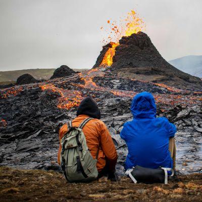 Tre personer som sitter och tittar på vulkanutbrottet på Island