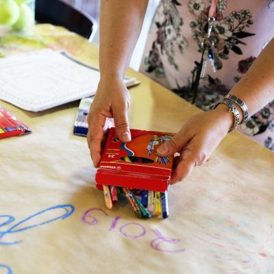koulukuraattori Sari Moisas valmistelee puuhapöytää Tikkurilan koulun lukiolaisille