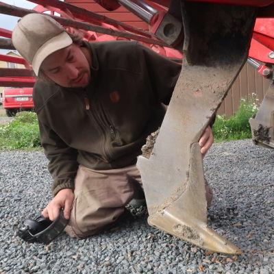 Anders Abrahamsson på knä, han synar traktorplogen som drog av elkabeln.