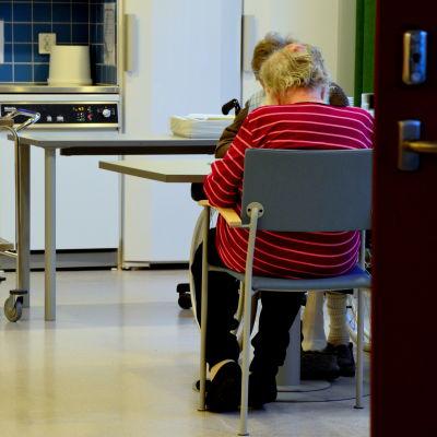 Ett par äldre personer sitter vid ett bord. I bakgrunden syns ett kök.