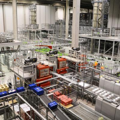 Vy inifrån logistikcentral. En massa rullband och produkter som åker förbi samt några arbetare i orange kläder synns.