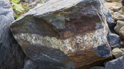 En stor mörkgrå sten med glimrande kopparröd färg i mitten och ett ljust streck..