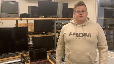 En man med glasögon och munkjacka står intill ett kontrollbord i en tv-studio.