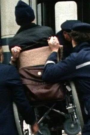 En rullstol lyfts in i ett snälltåg, 1985