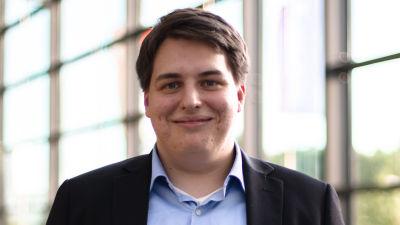 En man med svart kostym och blå skjorta ser in i kameran. Han är fotad inomhus, i bakrgunden stora fönster genom vilka grönt syns.