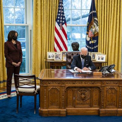 Joe Biden allekirjoittaa työpöytänsä äärellä. Kamala Harris ja Lloyd Austin katsovat vierestä.