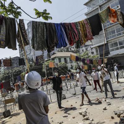 Myanmarin Yangonissa mielenosoittajat ripustivat barrikadien ylle naisten perinteisiä asuja. Asujen alta kävelemisen uskotaan vanhojen perinteiden mukaan aiheuttavan miehille huonoa onnea.