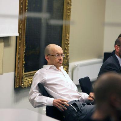 Peter Mangs plus några andra män sitter vid ett bord.