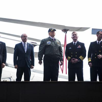 Donald Trump iklädd flygarjacka och skärmmössa på hangarfartyget Gerald R. Ford.