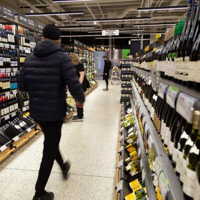 Alkon myymälän sisällä pulloja hyllyissä. Miesasiakas tummansinisessä toppatakissa ja musta pipo päässä on juuri astunut kameran takaa kuvaan reippaasti kävellen hyllyjen välistä käytävää pitkin. Miehen liike on tallentunut epäterävänä.