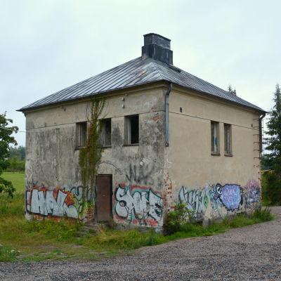 Ett gammalt kvadratformat hus med graffiti på väggarna.