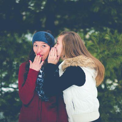 Tyttö kuiskaa toiselle tytölle jotain