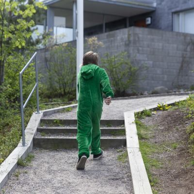 Lapsi juoksee pihatietä ylös.